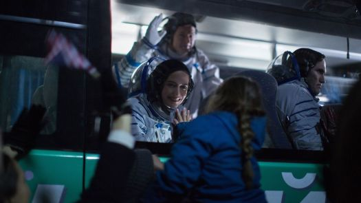 Eva Green, in full astronaut gear, reaches out for her daughter through a glass pane in Proxima