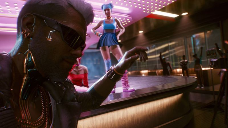 Jackie, la tua partner in Cyberpunk 2077, di fronte a una ballerina da tavolo in una discoteca.