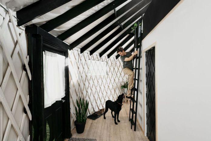 В интерьере юрты есть черная лестница, которая ведет к возвышенной круглой кровати. Мужчина взбирается по лестнице и смотрит вниз на черную собаку, лежащую на земле.