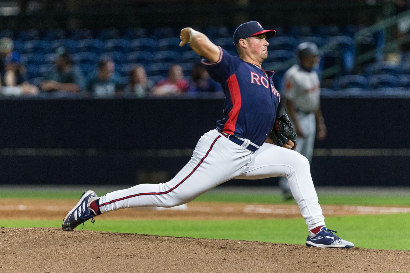 Indigo Diaz, right handed pitcher, delivers a pitch in a night game for the Rome Braves. The image is taken from the third base side, his landing is complete and he has begun bringing his hand forward. The ball is behind his head and is in a slider grip.