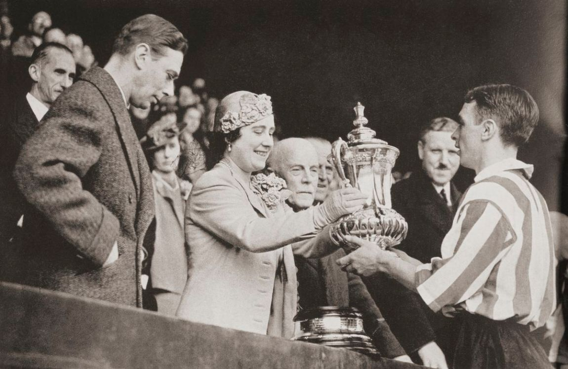 King George VI and Queen Elizabeth presenting the cup to Raich Carter, the Sunderland captain after his team's victory at Wembley in 1937