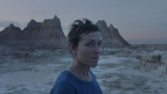 Seorang wanita kulit putih berdiri dengan latar belakang Badlands, dengan senyum kecil di wajahnya.