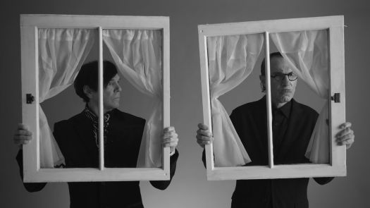 Russell and Ron Mael of Sparks, dressed entirely in black. hold up window frames and peer through them in The Sparks Brothers