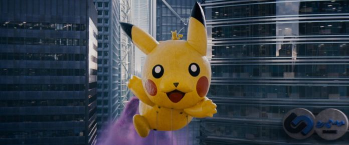 A large Pikachu balloon floats above a city in a parade