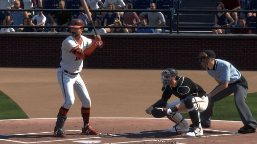 A player batting lefthanded in a brown-and-orange uniform waits on a pitch along with the game's catcher and home plate umpire in MLB The Show 21
