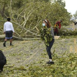 Volunteers remove tree branches blocking 900 West in Salt Lake City on Tuesday, Sept. 8, 2020. High winds brought the branches down.