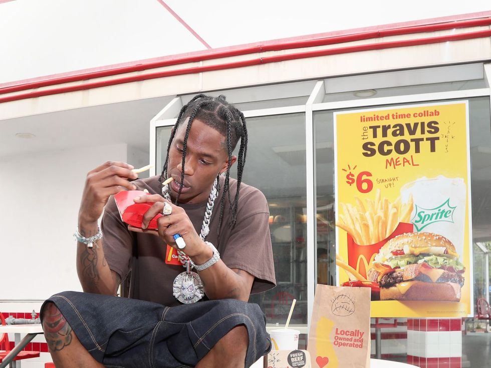 Travis Scott sitting on an outdoor table in front of a McDonald's, holding a carton of fries.