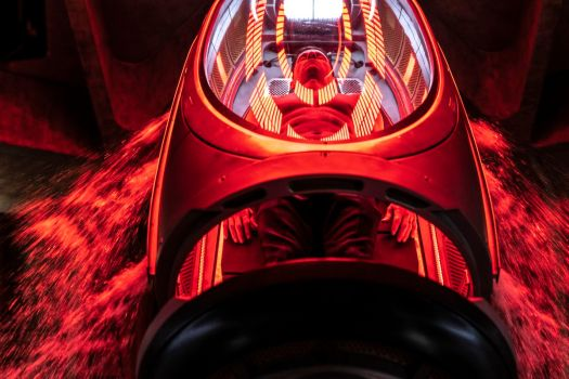 Mark Wahlberg lies shirtless inside a glass and metal capsule bathed in red and yellow light in Infinite