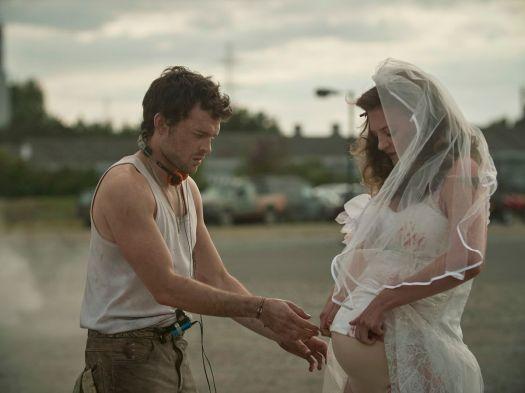 Alden Ehrenreich as John the Savage helps Lara Peake as Madysun in Brave New World.
