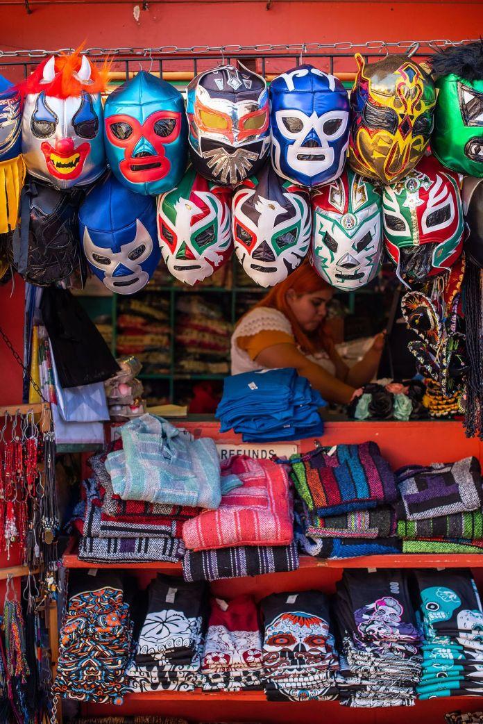 Vendedor en la calle Olvera que vende máscaras de luchador, camisetas y más.