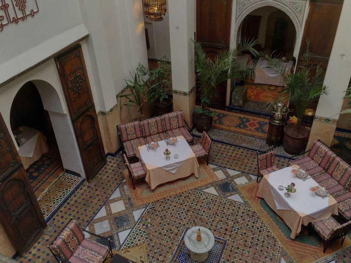 From above, a tall open-air atrium with several tables set around couches, tiled floors, fountain, potted plants, and tall rounded doorways