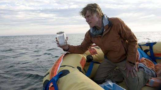 Robert Redford, looking sunburned and battered while kneeling in a lifeboat, holds up a jar with a little bit of water in it in All Is Lost.