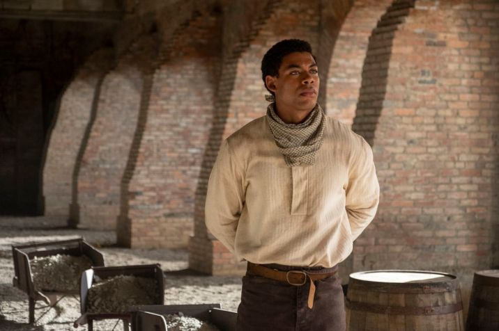 A calm, proud-looking Black man with his hands behind his back stands in a train station, looking offscreen