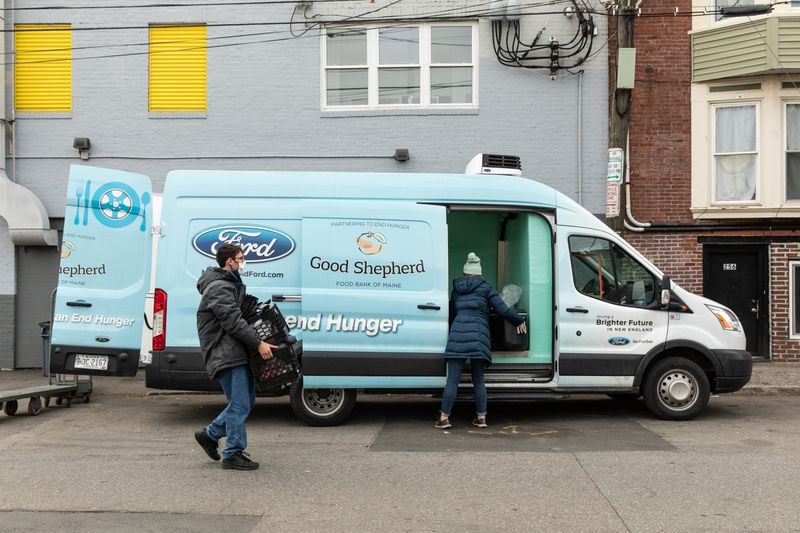 A man carries crates toward a light blue van where a woman is loading goods