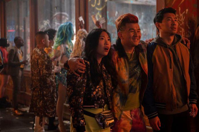 Awkwafina como Katy, e Simu Liu como Shang, olham com a boca aberta em choque para algo fora do quadro como Ronny Chieng enquanto Jon Jon abraça os dois enquanto parece divertido.