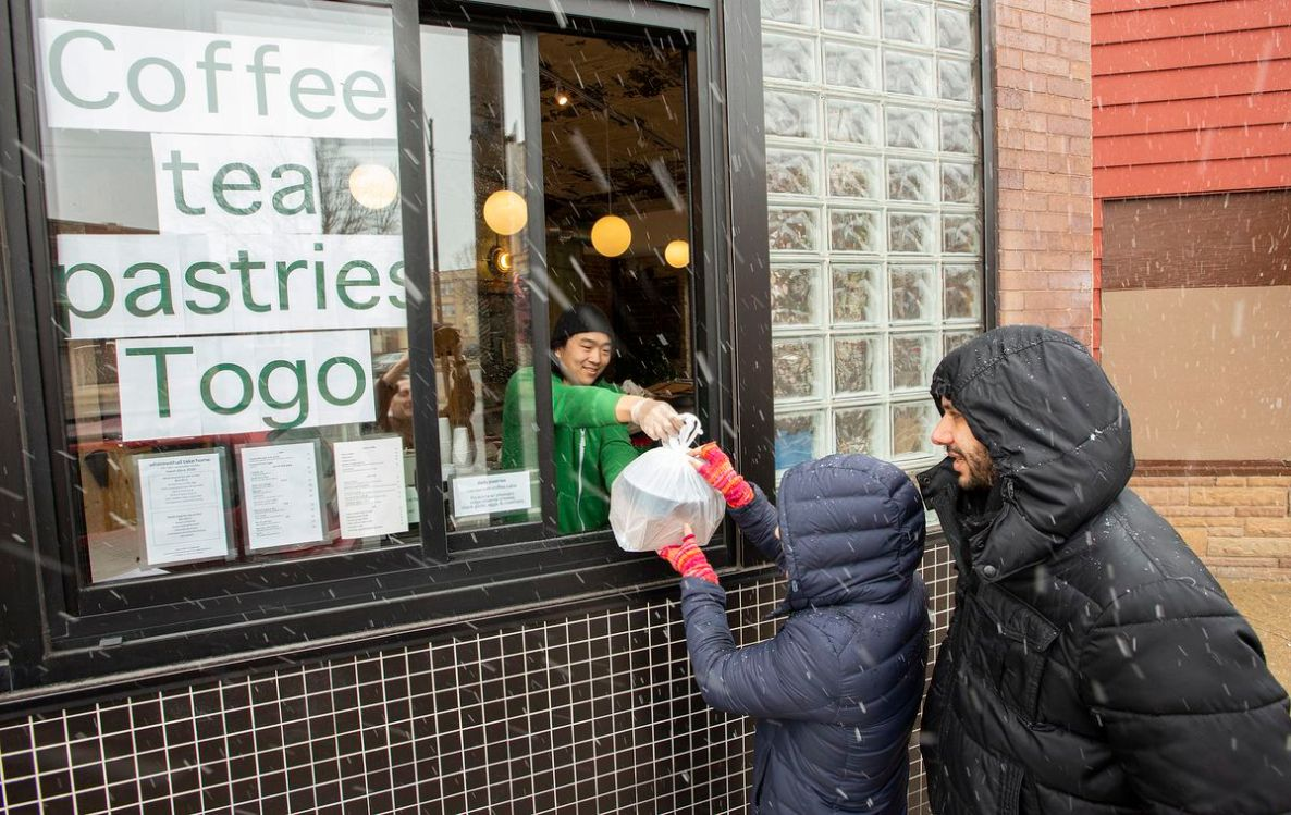A person hands a bag through a window to a child in the falling snow with a parent watching.
