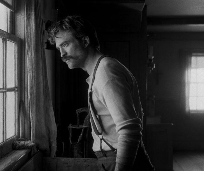 Ephraim (Pattinson) regarde par la fenêtre.