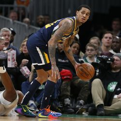 Utah Jazz's Jordan Clarkson gathers in the ball next to fallen Boston Celtics' Robert Williams III during the fourth quarter of an NBA basketball game Friday, March 6, 2020, in Boston.