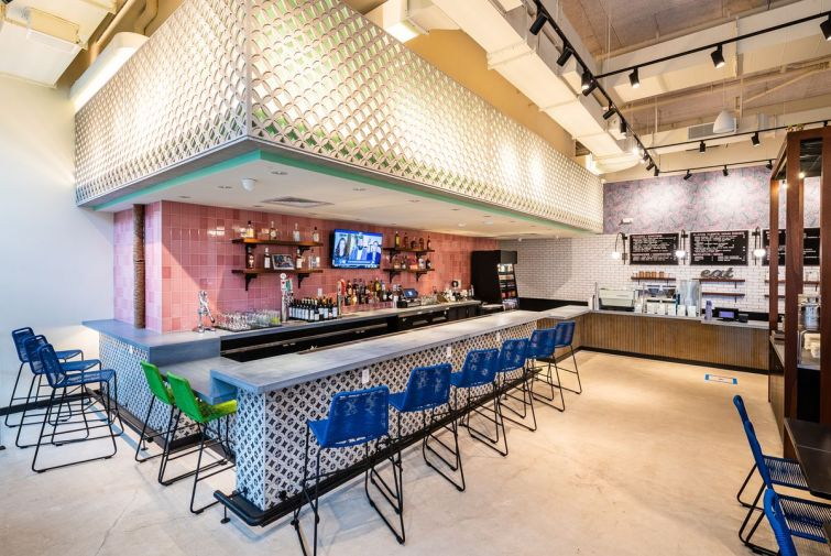 A white patterned bar sits in front of a pink tiled wall inside La Famosa