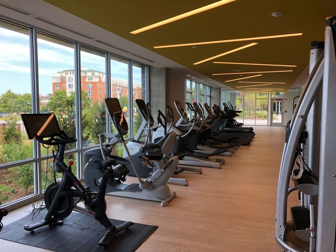 Running of stage machines, fitness bikes, and tread mills in front of a window in a gym.