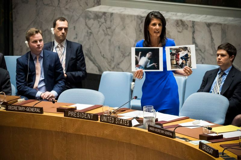 US Ambassador to the UN Nikki Haley holds up photos of victims of the Syrian chemical attack during a meeting of the United Nations Security Council on April 5, 2017.