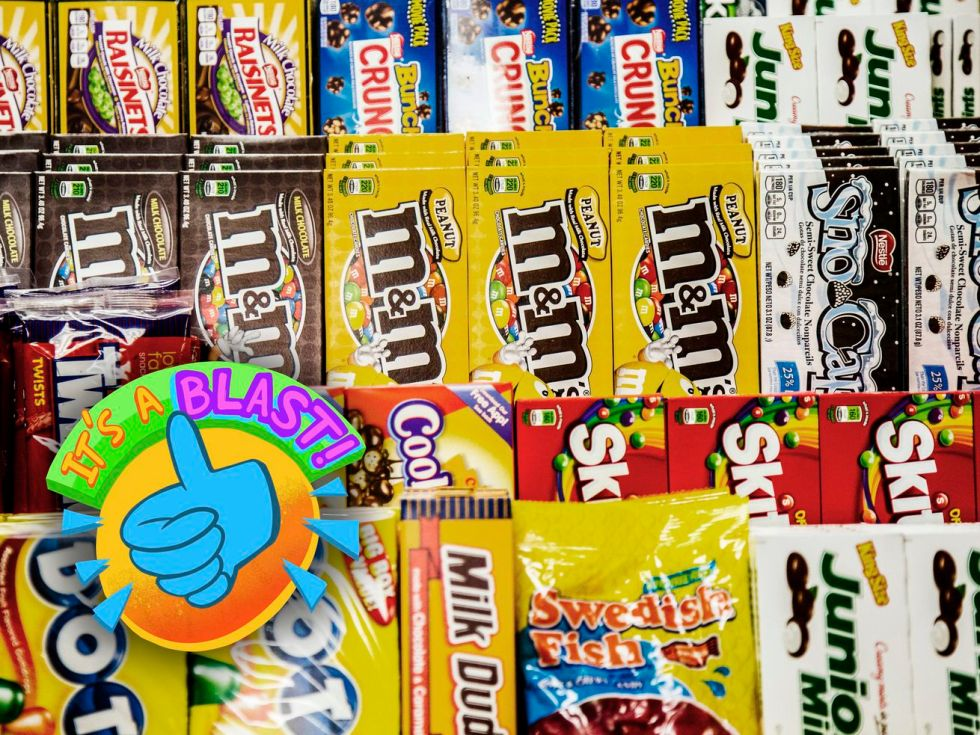 Rows of boxed snacks — M&M's, Sno-Caps, Skittles, Junior Mints, and more — lined up behind a counter.