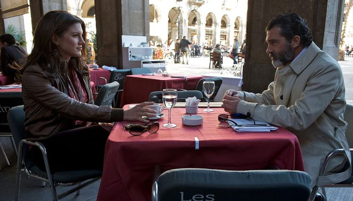 Antonio BanderasandGina Carano share a look over a cafe table in a screenshot from Haywire
