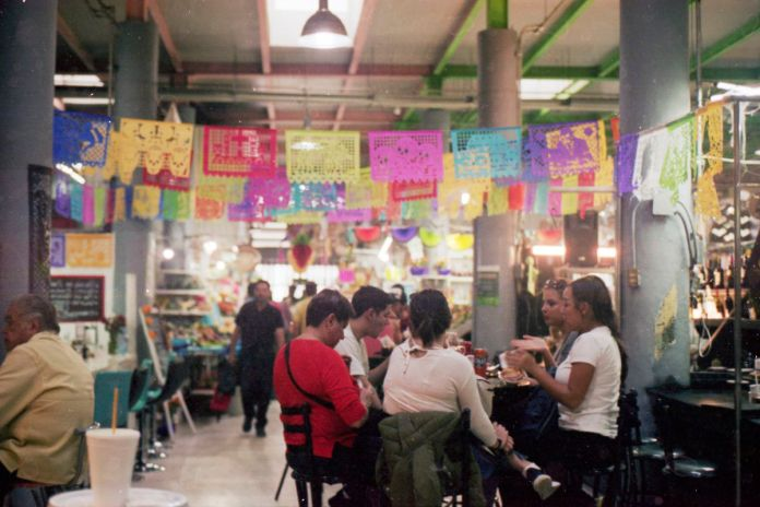 A table of women sit and eat beneath colorful decorations