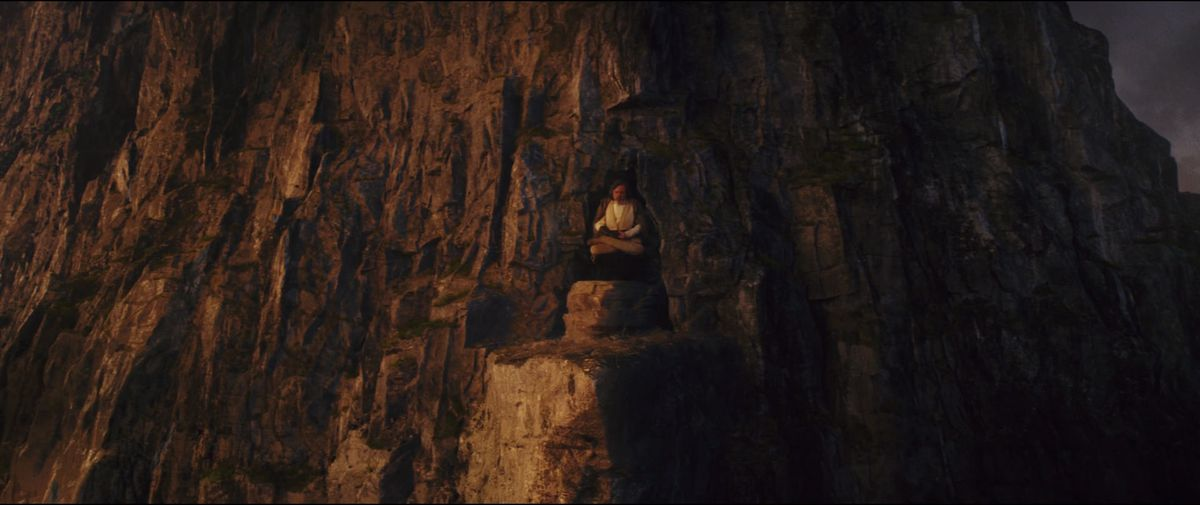 luke skywalker sits crosslegged hovering over the rocks of ach-to in last jedi
