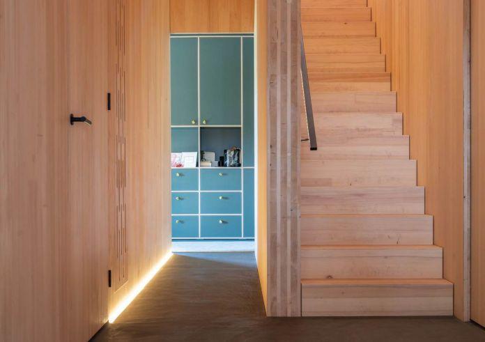 Деревянная лестница ведет на второй уровень, в то время как вниз по коридору вы можете увидеть бирюзовый встроенный шкаф с белой отделкой.