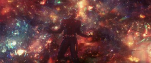 Ant-Man floats in the multicolored, cloudy Quantum Realm in Ant-Man and the Wasp