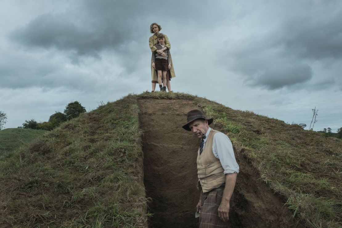 Carey Mulligan stands at the top of an excavation in a grassy mound as Ralph Fiennes explores it from below in The Dig
