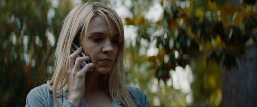 Brea Grant on her cell phone in Lucky
