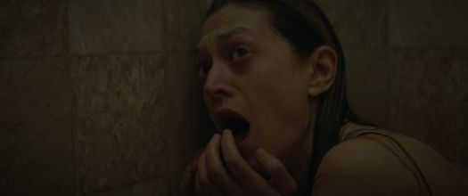 A wet woman hunched in the shower screams, looking at something offscreen