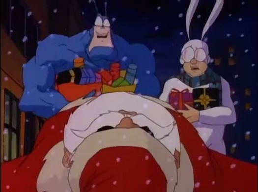 The Tick and Arther look aghast over the body of Santa, in The Tick (1994).