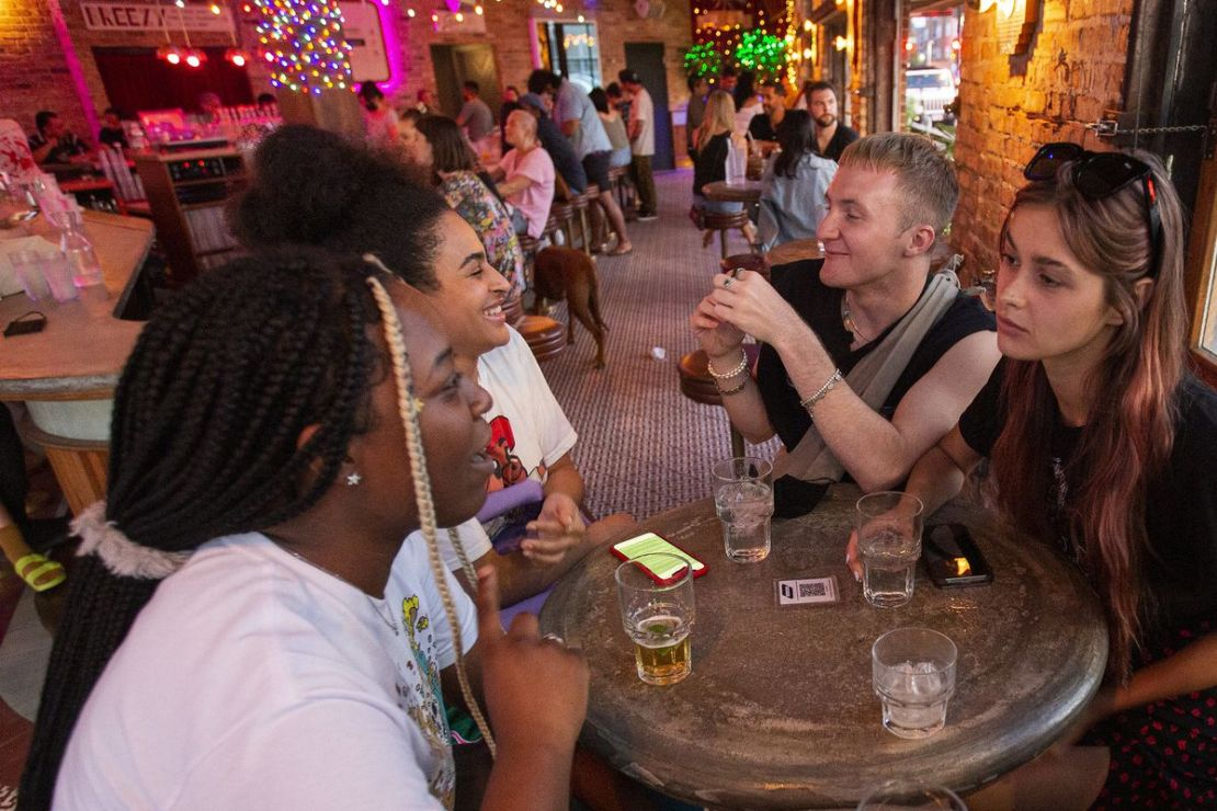 A group of four people gather around a round table at a bar.
