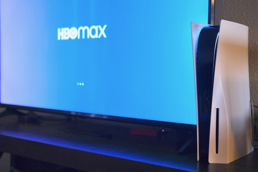 A PlayStation 5 in front of a TV showing HBO Max