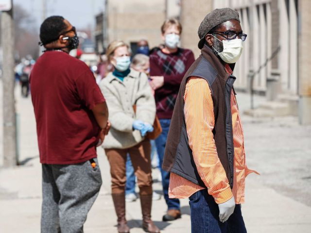 People in face masks wait in line to vote in Wisconsin.