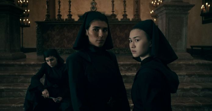 Three young women in all-black nun habits and wimples look suspiciously offscreen in Netflix's Warrior Nun.