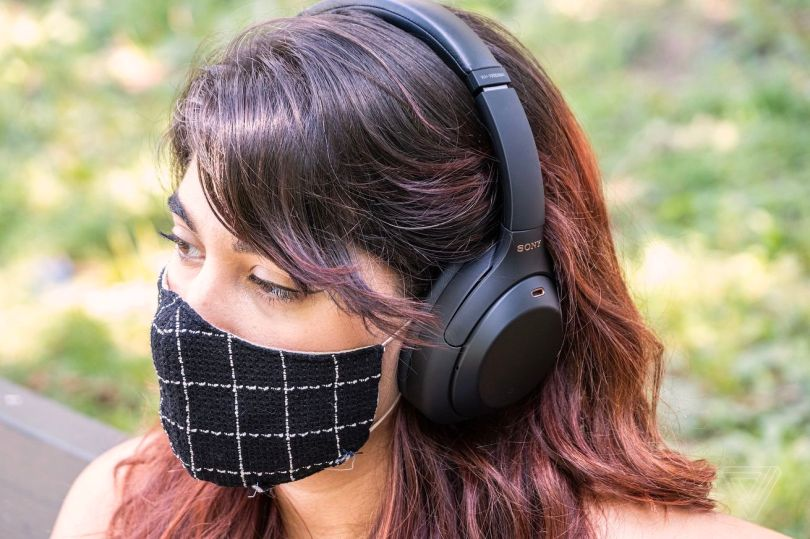 A woman wearing headphones and a mask