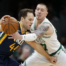 Boston Celtics' Daniel Theis, right, tries to knock the ball away from Utah Jazz's Bojan Bogdanovic during the fourth quarter of an NBA basketball game Friday, March 6, 2020, in Boston.