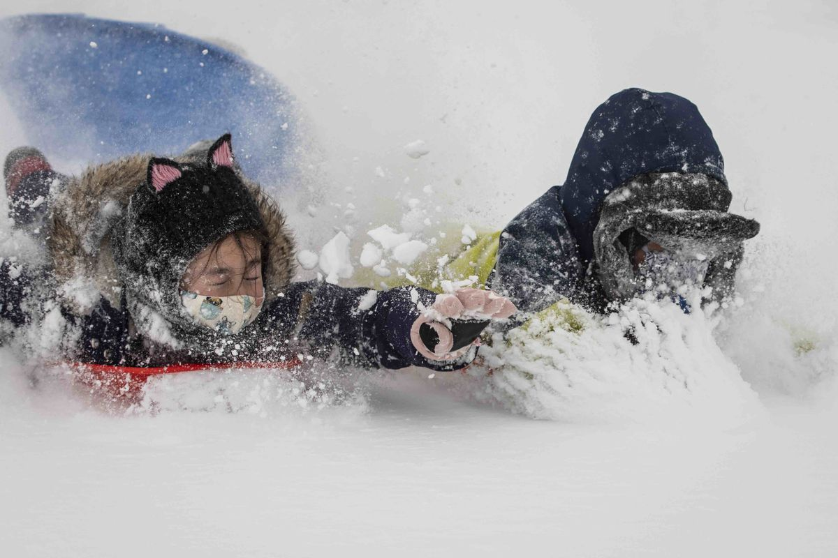 Nari Berthusen, 9, and Eito Tabion, 8, sled down Cricket Hill near Montrose Beach on the North Side after several inches of snow fell overnight across Chicago, Monday afternoon, Feb. 15, 2021.