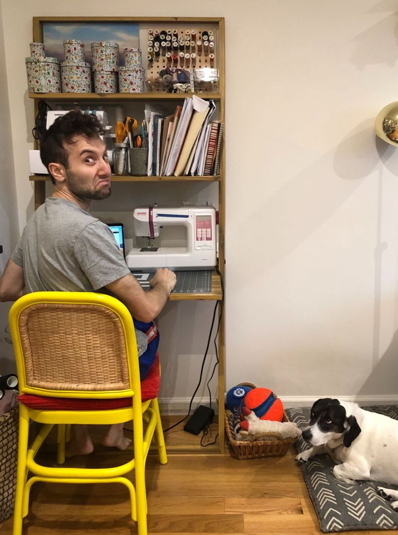 Seth working at his wife's sewing desk while dog Trudy looks on
