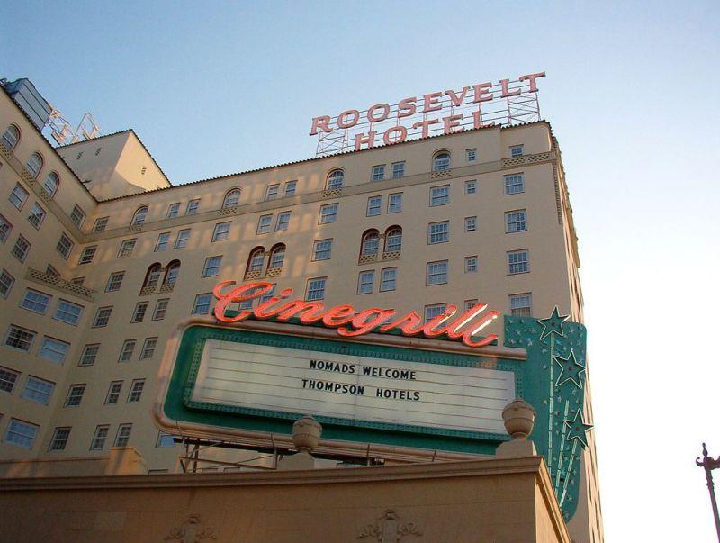 L'extérieur de l'hôtel Hollywood Roosevelt.  La façade est bronzée.  Au premier plan, une pancarte indique: Cinegrill, bienvenue aux nomades, hôtels Thompson.
