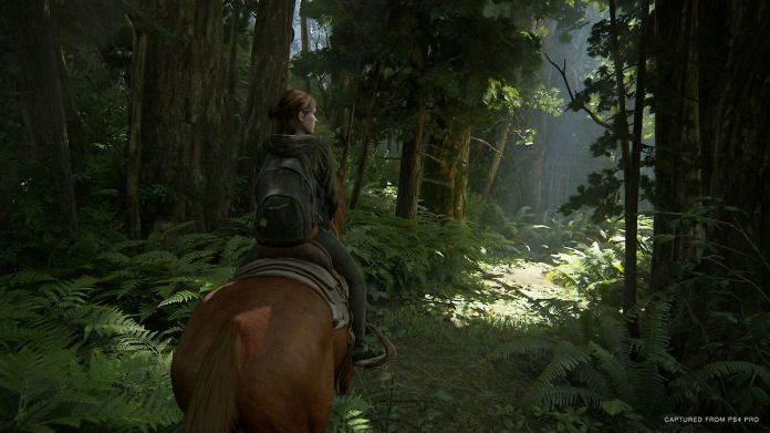 Ellie rides a horse through a forest in a screenshot from The Last of Us Part 2