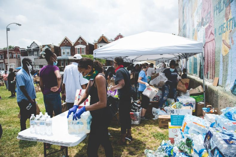 several people outside next to a mural and a table with bottled water, with cartons of bottled water and boxes of food and supplies piled on the grass