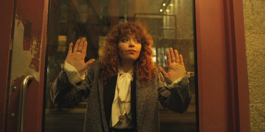 Natasha Lyonne presses her hands up against a glass door in Russian Doll