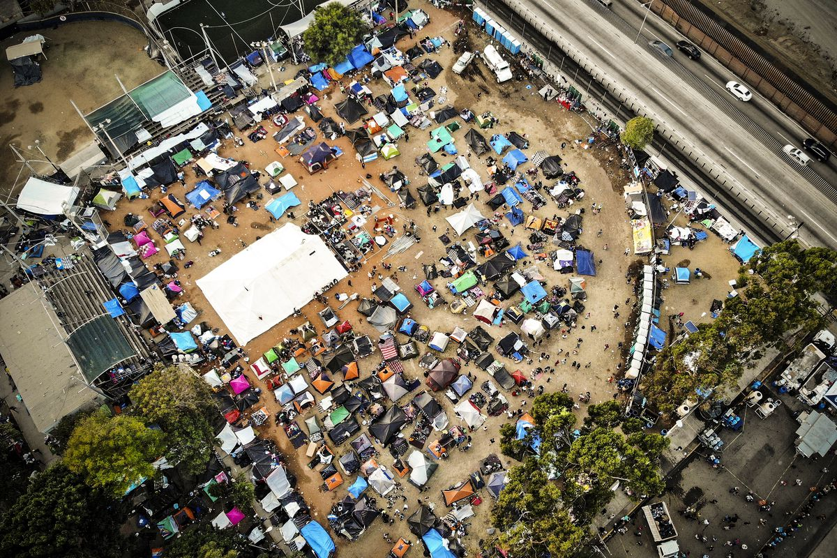 An aerial view of the temporary shelter set up for members of the 'migrant caravan', with a section of the U.S.-Mexico border barrier visible (TOP R), on November 24, 2018 in Tijuana, Mexico. Around 6,000 migrants from Central America have arrived in the