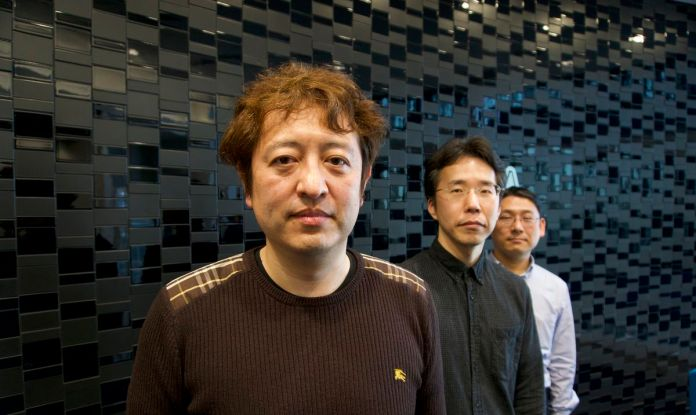 Three former Sega programmers stand in front of a black, tiled wall
