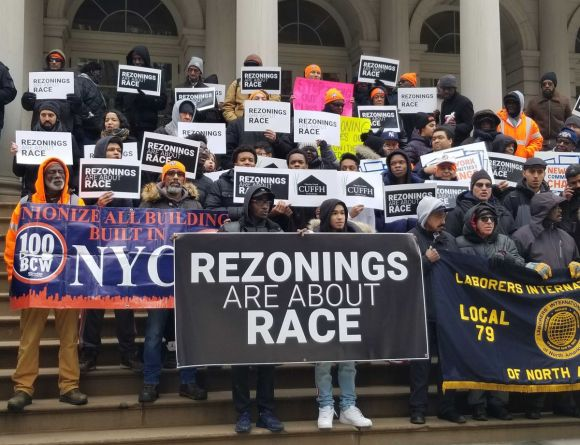 Housing advocates and elected officials rallied on the steps of City Hall to protest rezoning.